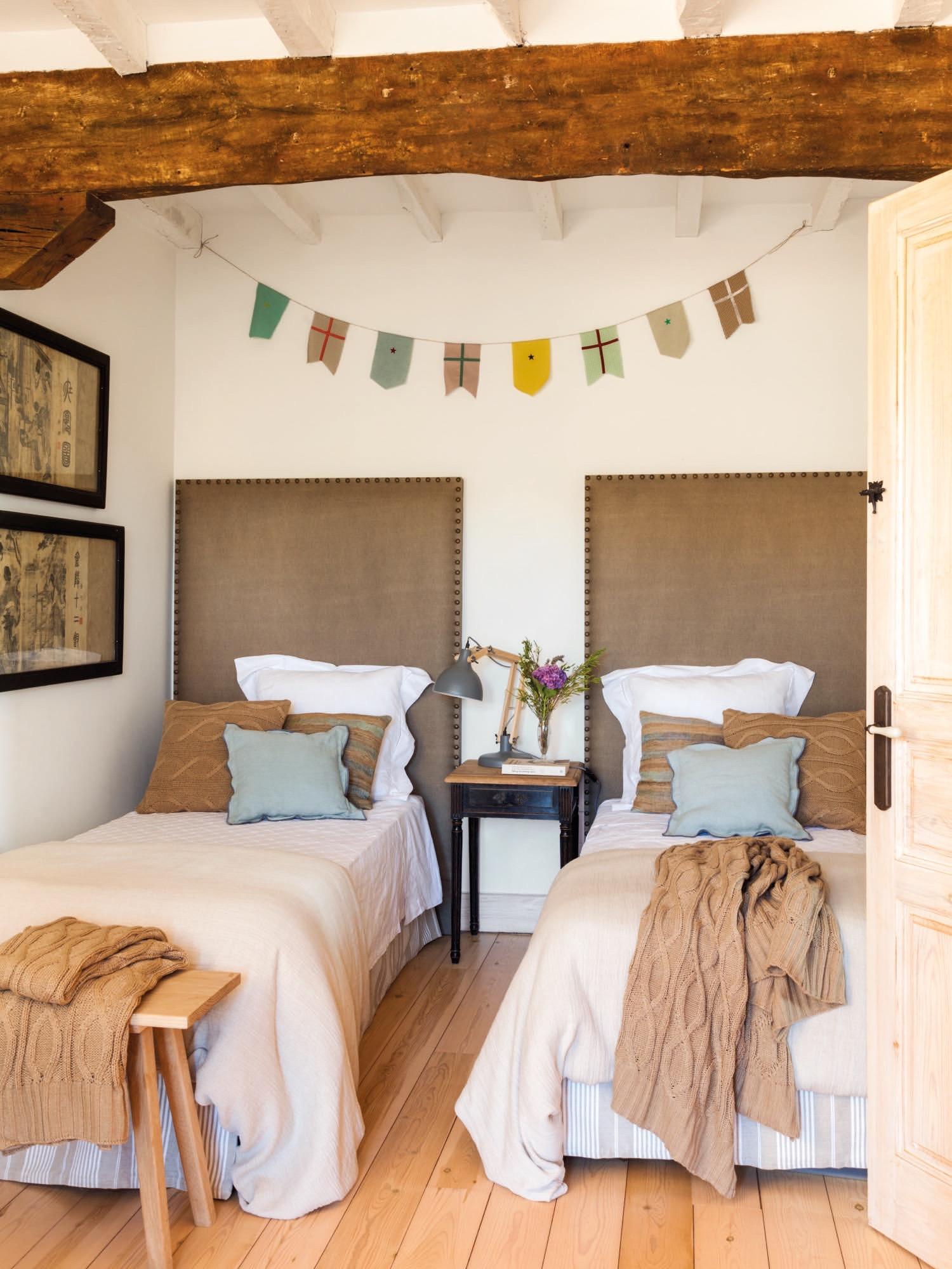 dormitorio juvenil en una casa rustica con cabeceros tapizados