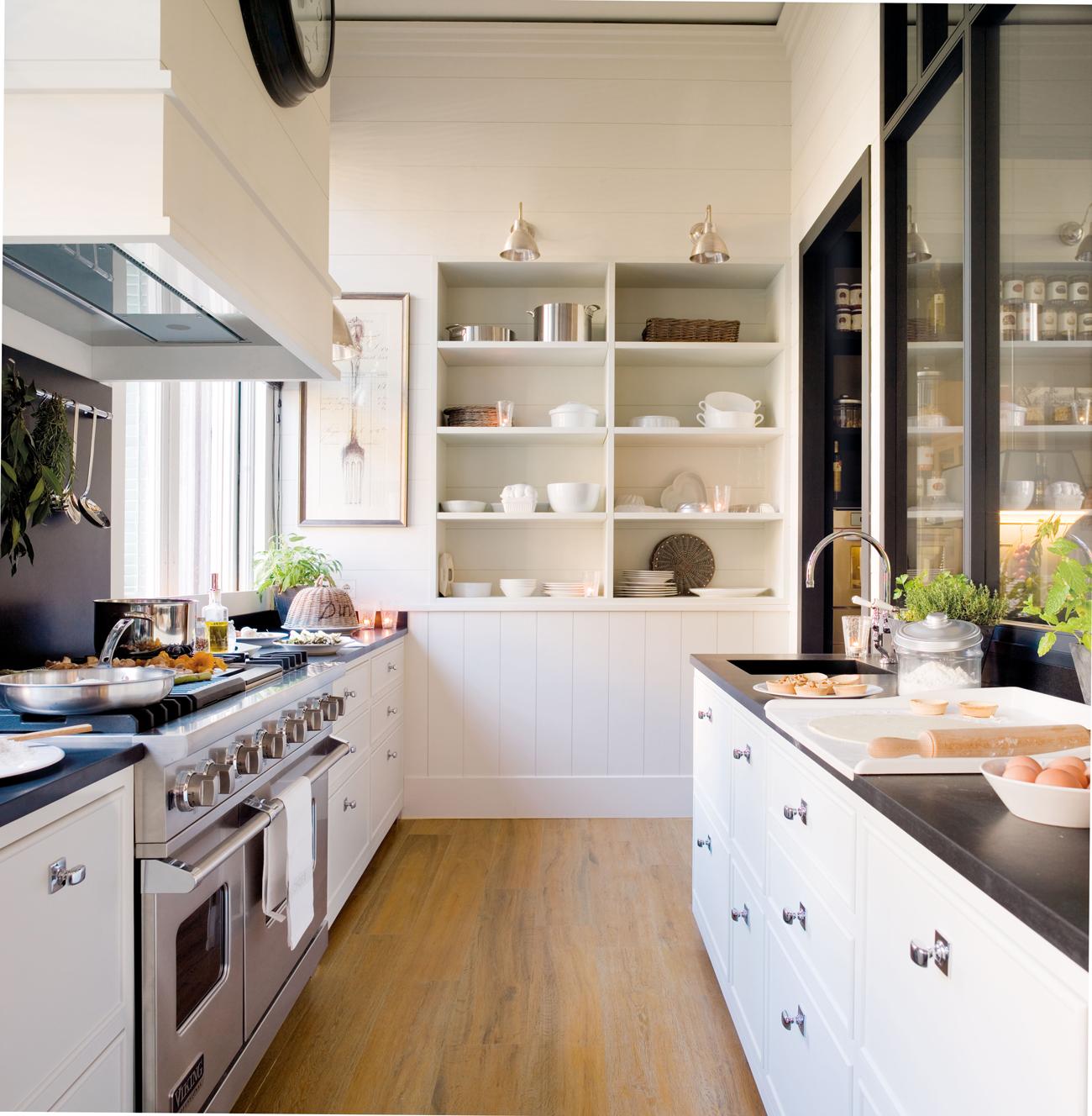 cocina blanca con encimera negra y cristalera negra