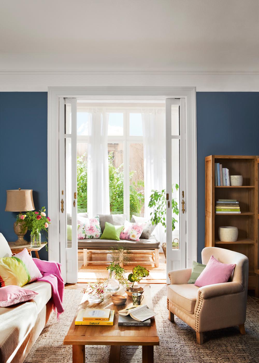 00404173. Salón clásico de puertas correderas blancas, paredes en azul intenso, sofás claros y cojines rosados y lámpara de lágrimas 00404173