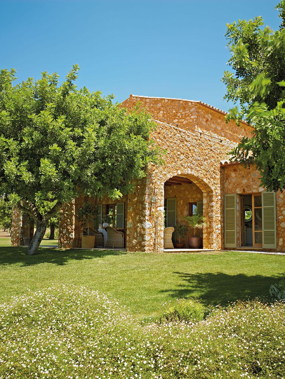 00323764. Fachada de la casa de piedras y porche con butacas de fibras junto al jardín_00323764