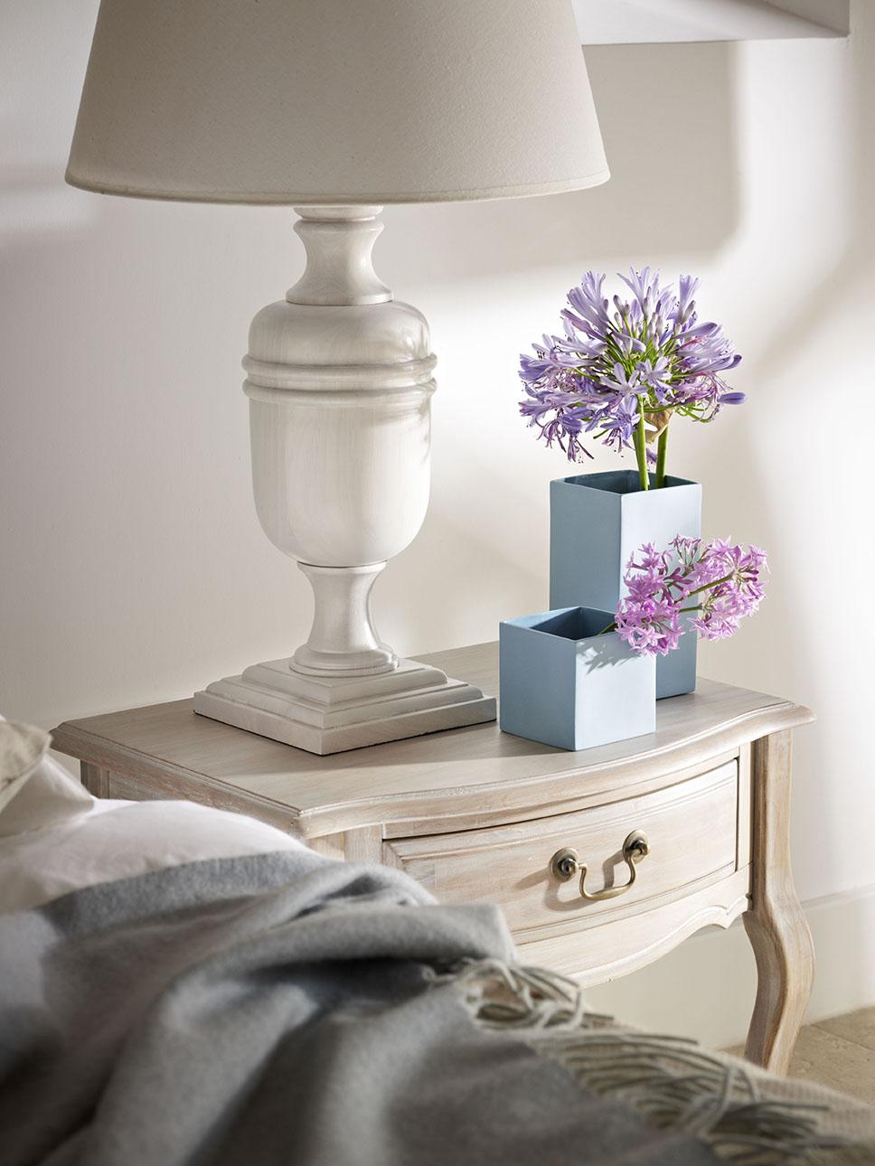 00326178 O. Flores de color lavanda en un jarrón azul claro y una lámpara blanca sobre la mesita de noche del dormitorio principal_00326178 O