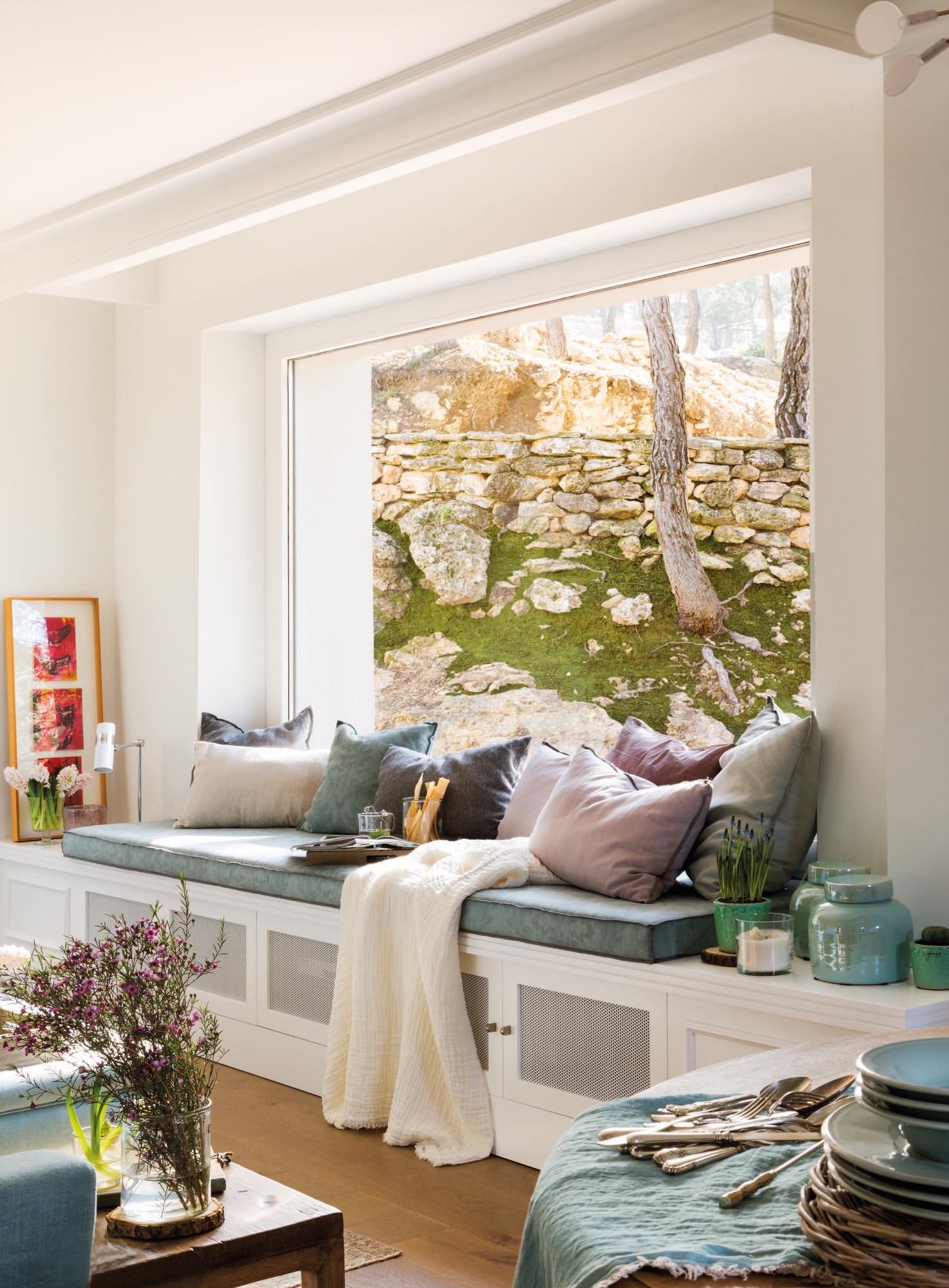 bancada con cojines junto a una ventana