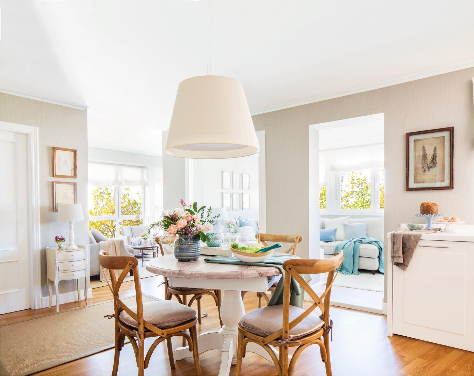 comedor con mesa provenzal en el centro de un piso con dos salitas de estar