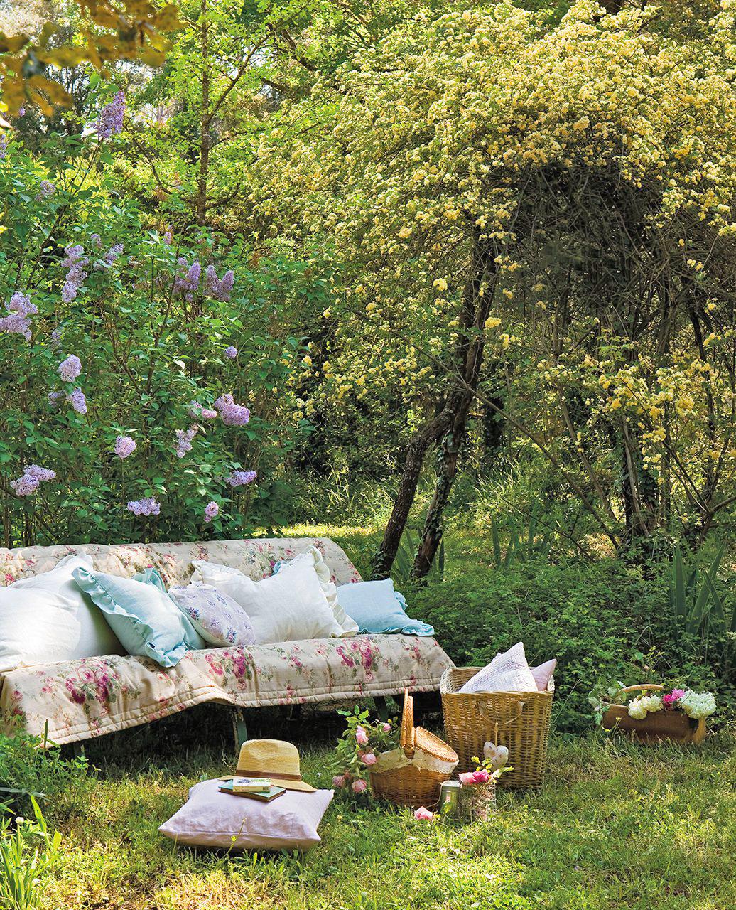 JARDIN banco cubierto con colcha y cojines en medio de un jardin de rosas 1036x1280