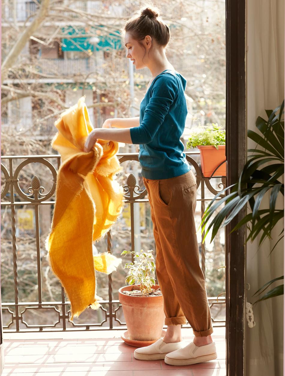 Chica sacudiendo plaid en el balcón_449289 O