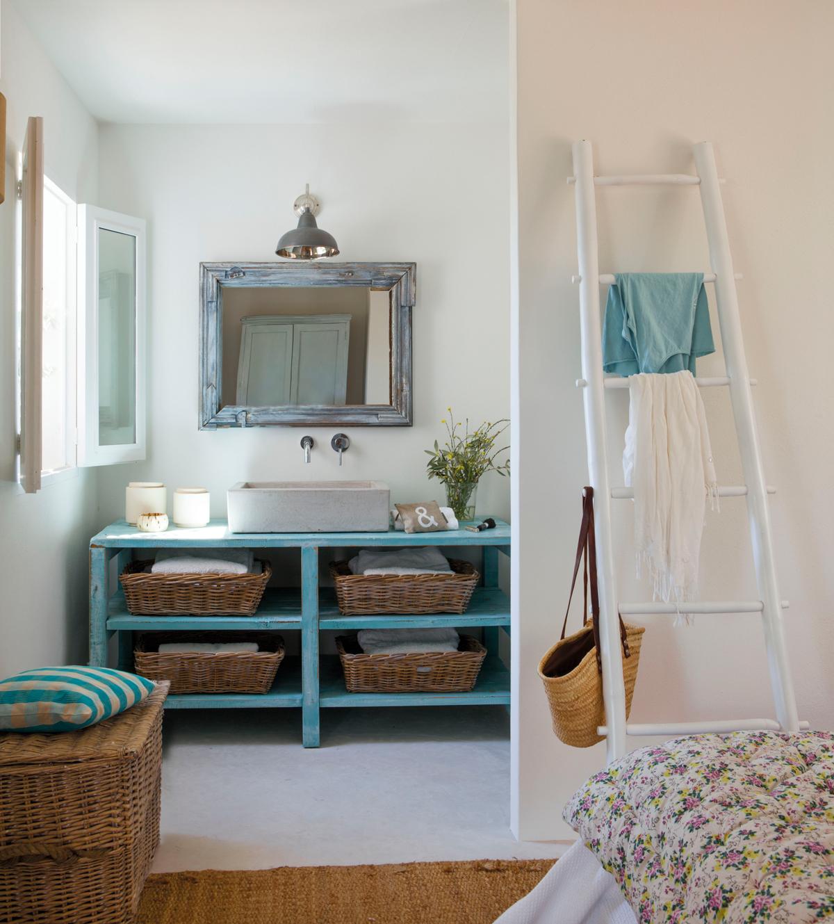 bao en suite con mueble de madera recuperado en azul cestas de mimbre tabique separador