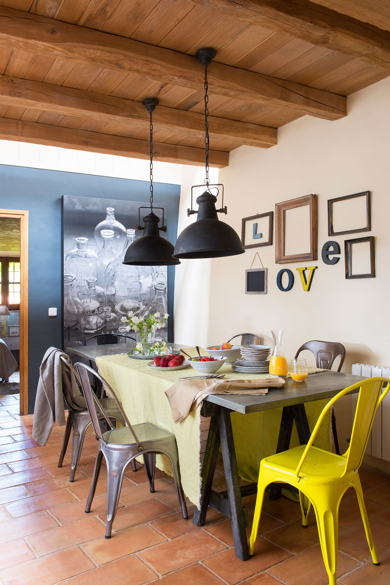 Comedor con pared negra y mesa y sillas de look industrial. Look industrial.