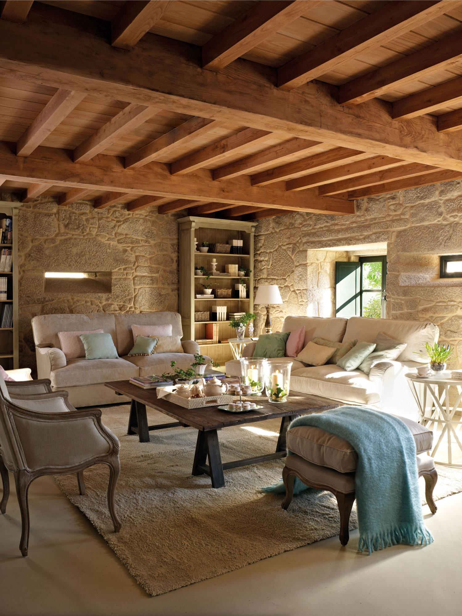 00315219. Salón con paredes de piedra y vigas de madera con sofás, butacas, puf y librerías_00315219