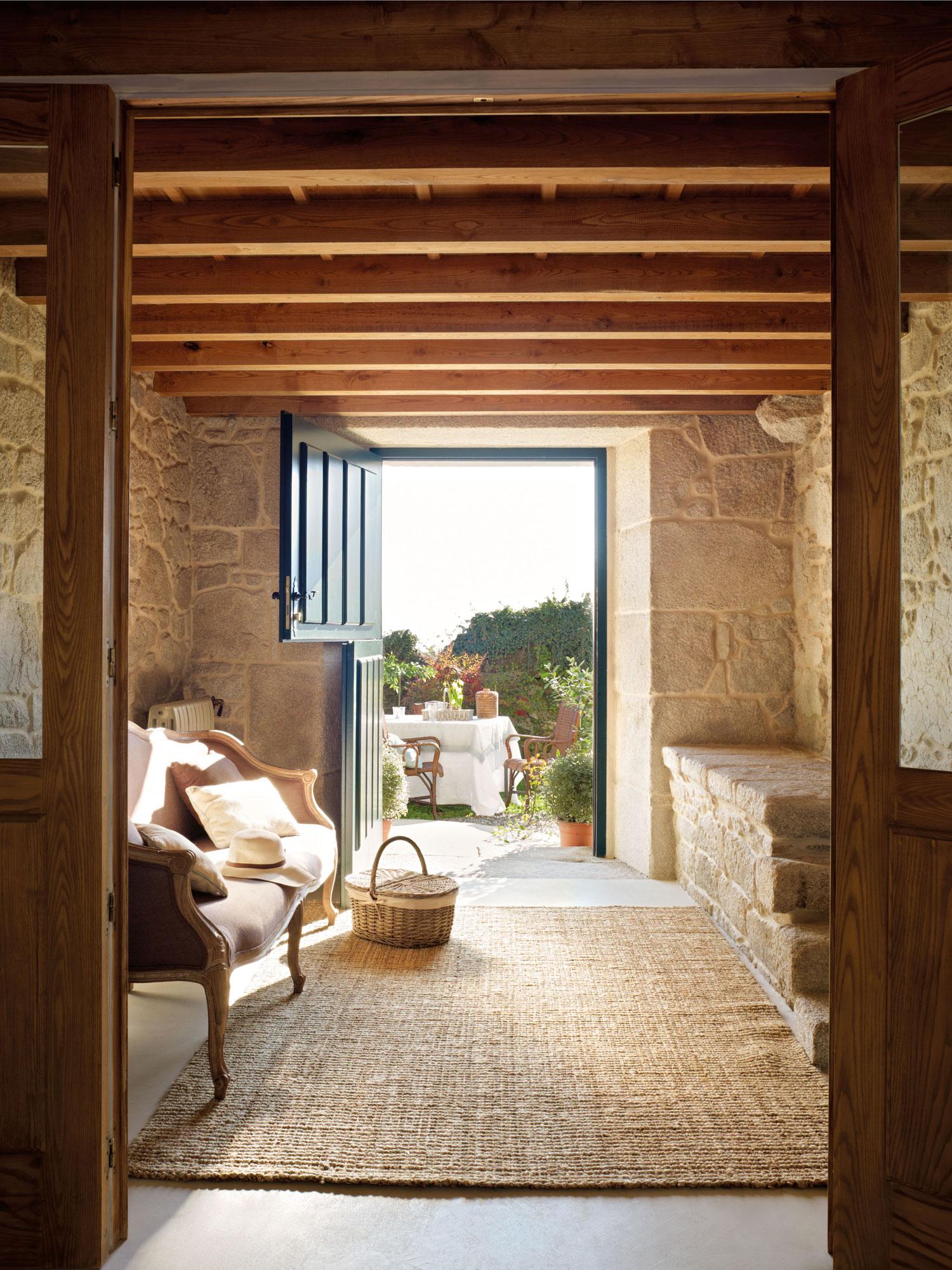 00315221. Entrada de la casa con muros de piedra y un banco sobre una alfombra de mimbre_00315221