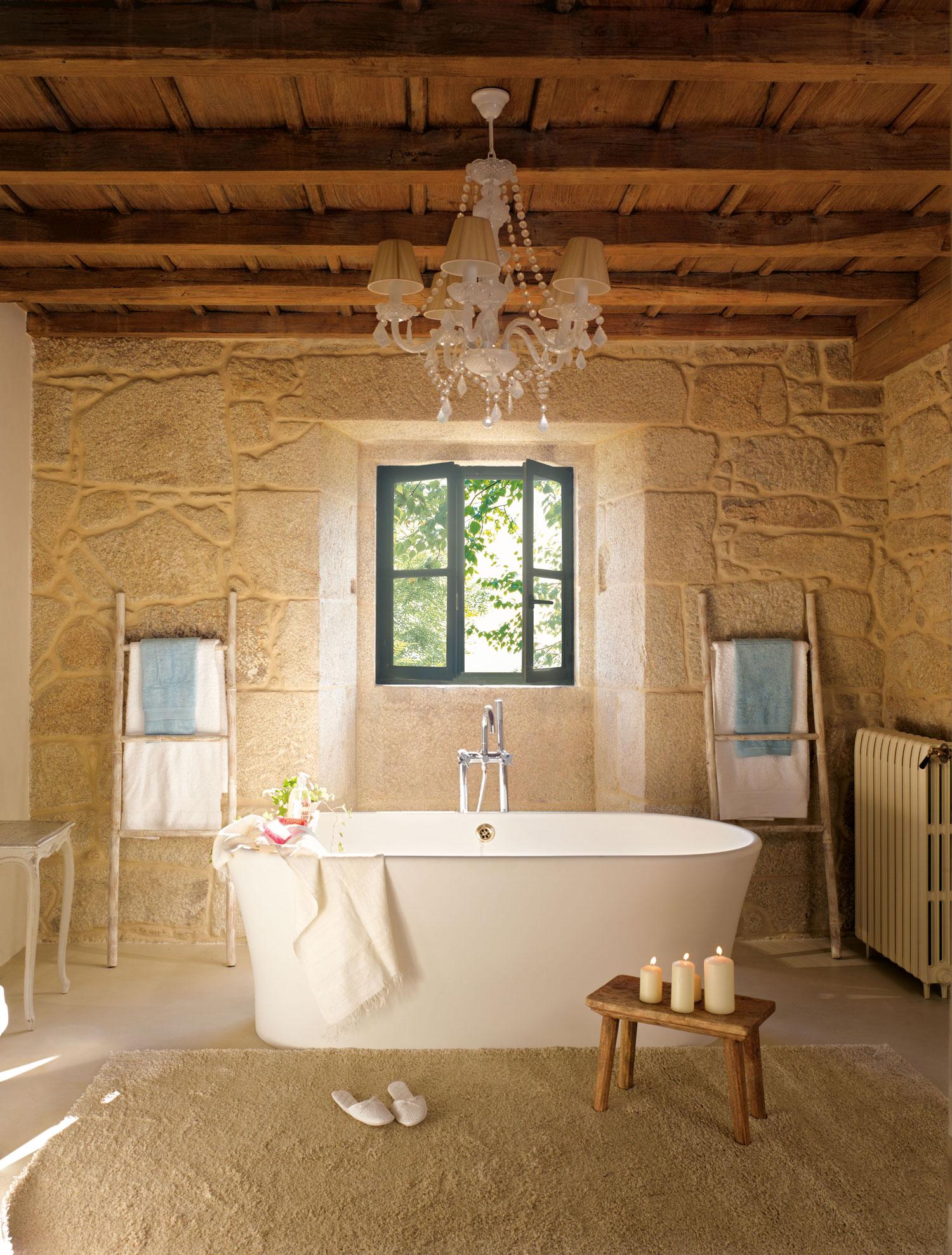 00315229. Baño de muros de piedra con una bañera en el centro y escaleras de toalleros a cada lado_00315229