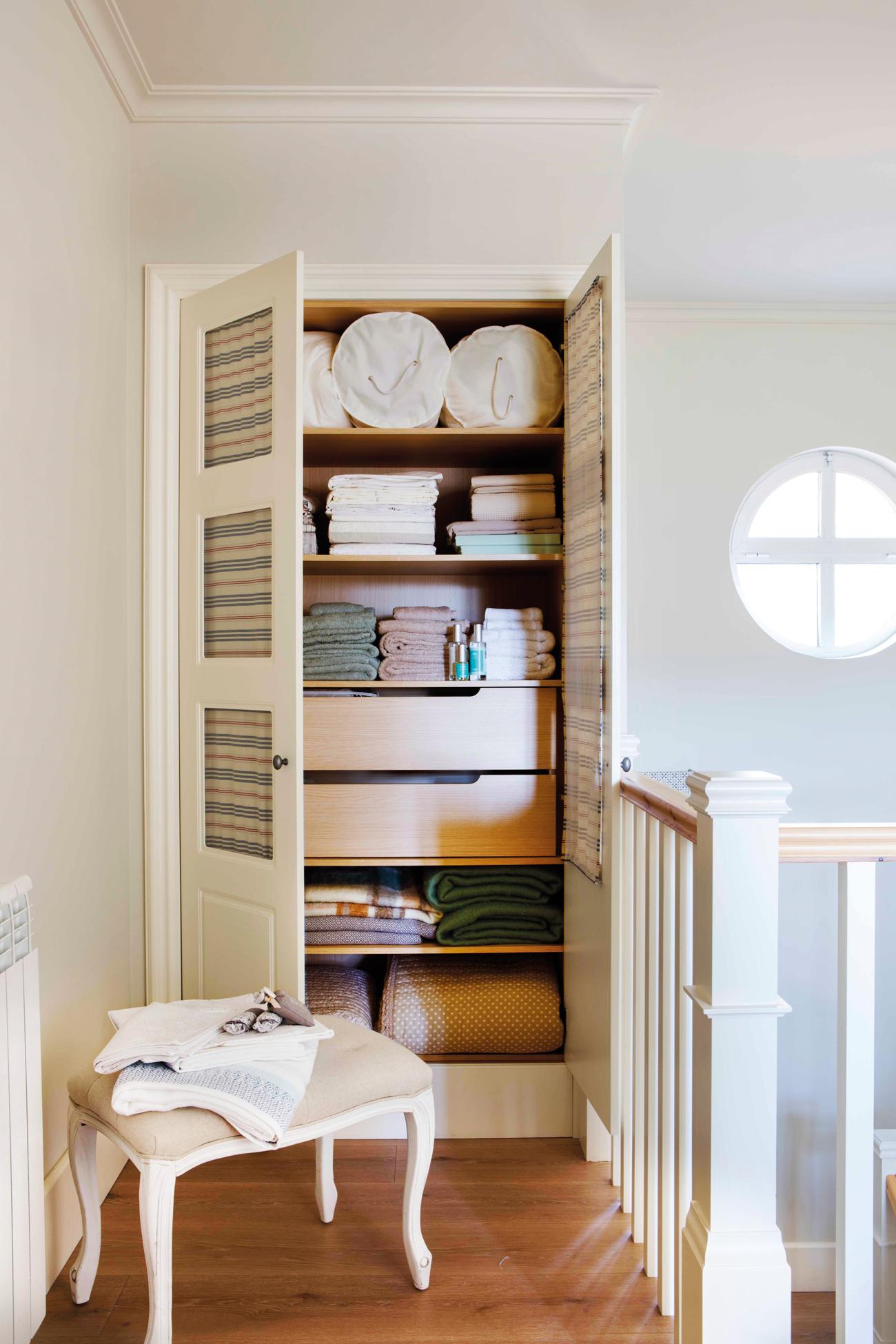 armario para la ropa blanca en descansillo junto a escaleras y banqueta