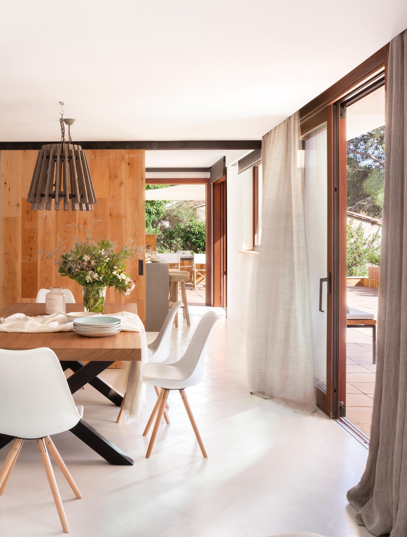 cocina con office con sillas de diseo y puerta corredera de madera con acceso al saln