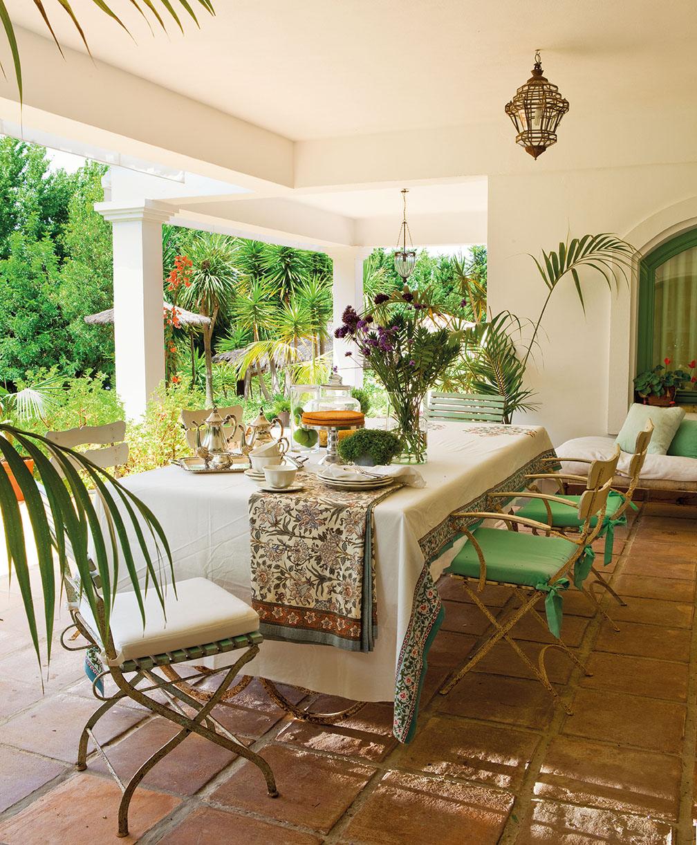 00324105. Comedor en el porche rodeado de plantas y con sillas de hierro con cojines en blanco y verde_00324105