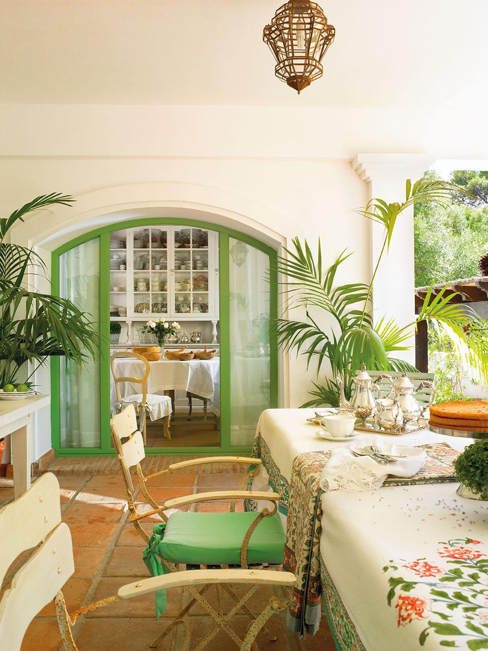 00324107. Comedor en blanco y verde con sillas de hierro en el porche_00324107