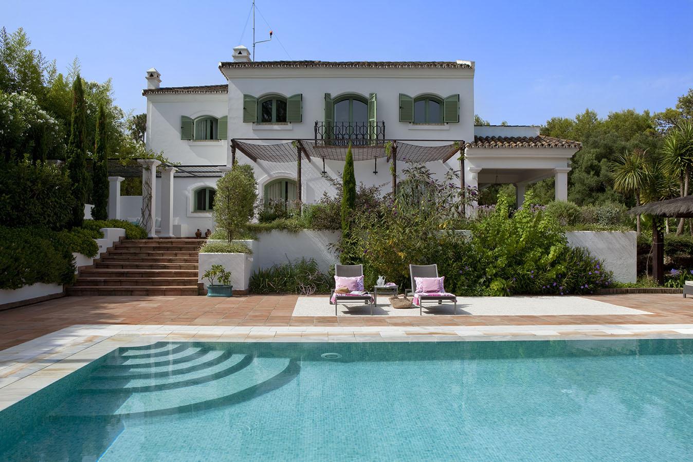 00324116 O. Fachada de la casa en blanco con porticones en verde y piscina con dos tumbonas_00324116 O