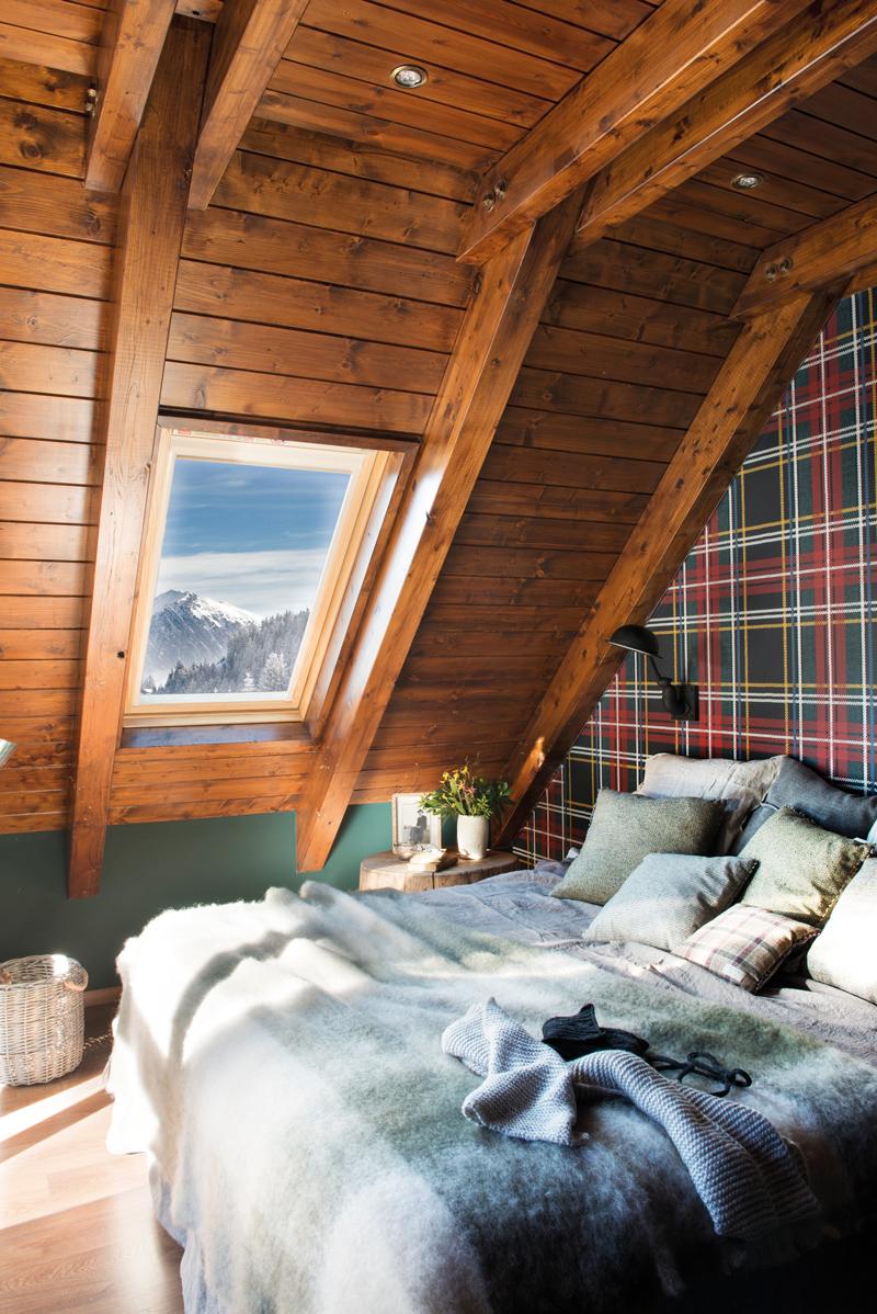 00447294. Dormitorio abuhardillado y rústico con techo revestido de madera oscura y pared entelada a cuadros 00447294