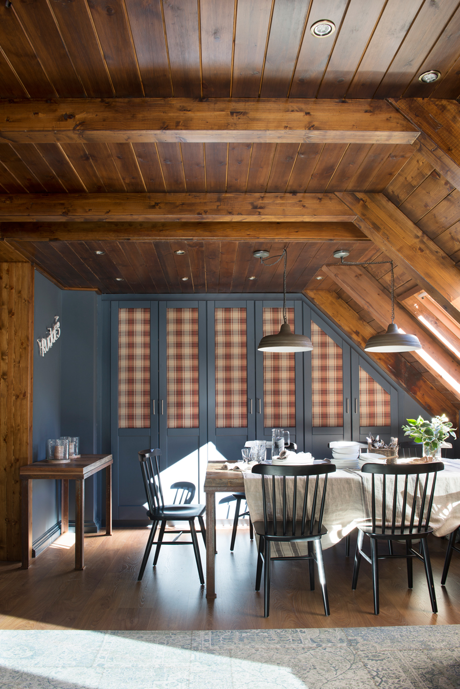 00447308 O. Comedor rústico con techo de madera, pardes en azul oscuro y armarios empotrados entelados con tela a cuadros 00447308 O