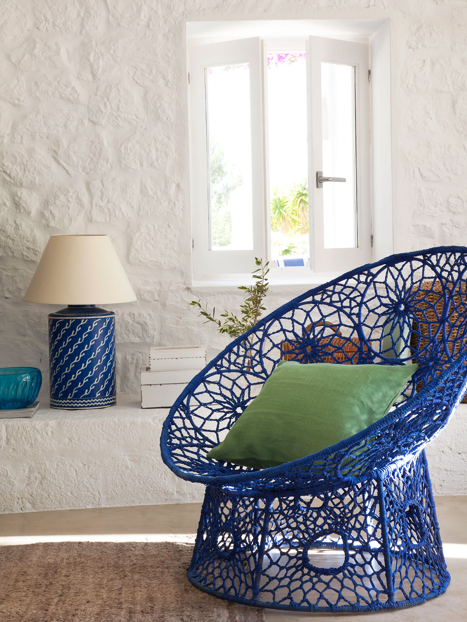 Semitoma de butaca azul en salón con paredes encaladas. Semitoma de butaca azul en salón con paredes encaladas_346886