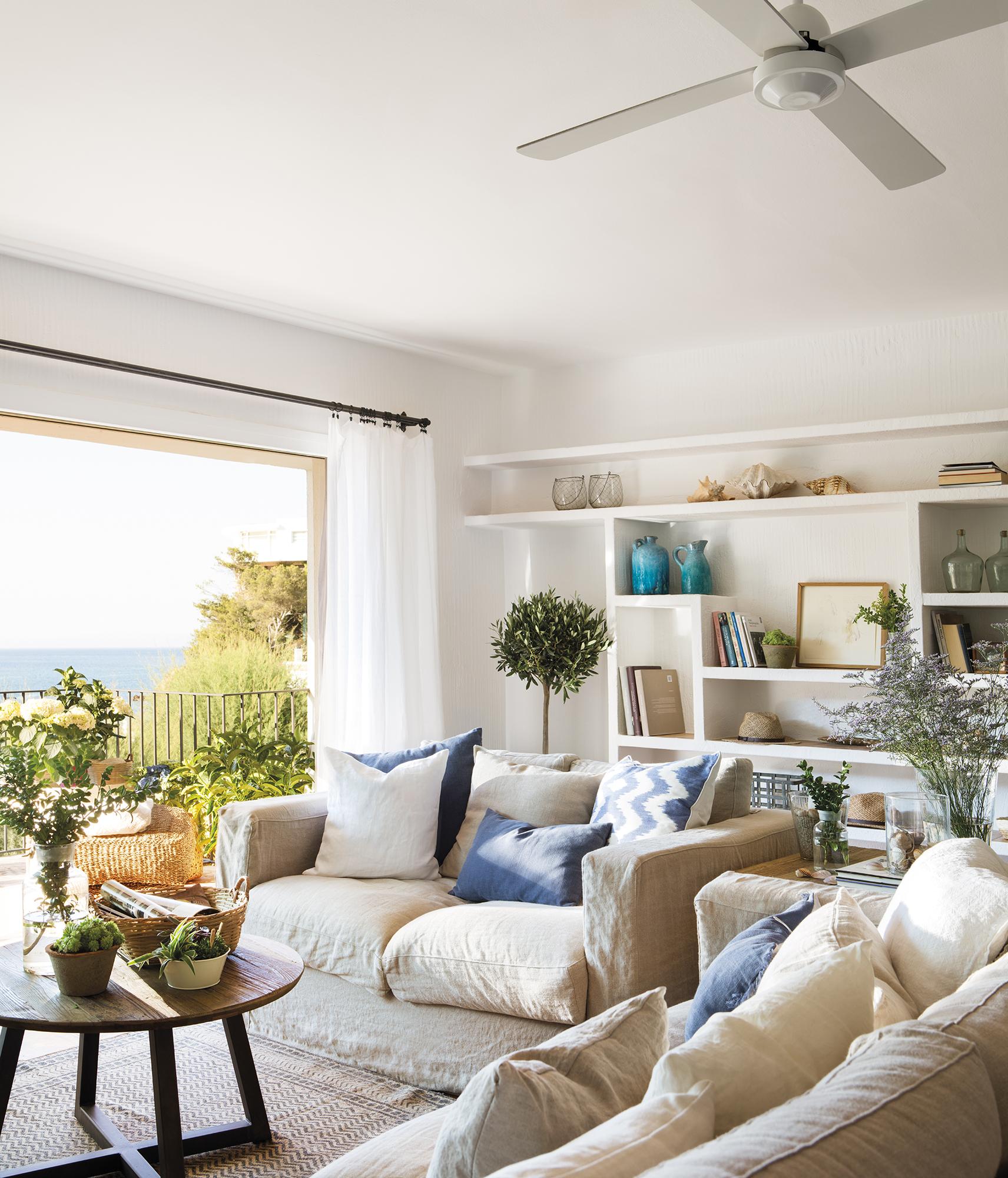 """PANO 0838-0839. Pequeño salón con dos sofás en """"L"""", estanterías blancas de obra al fondo y grandes ventanales"""
