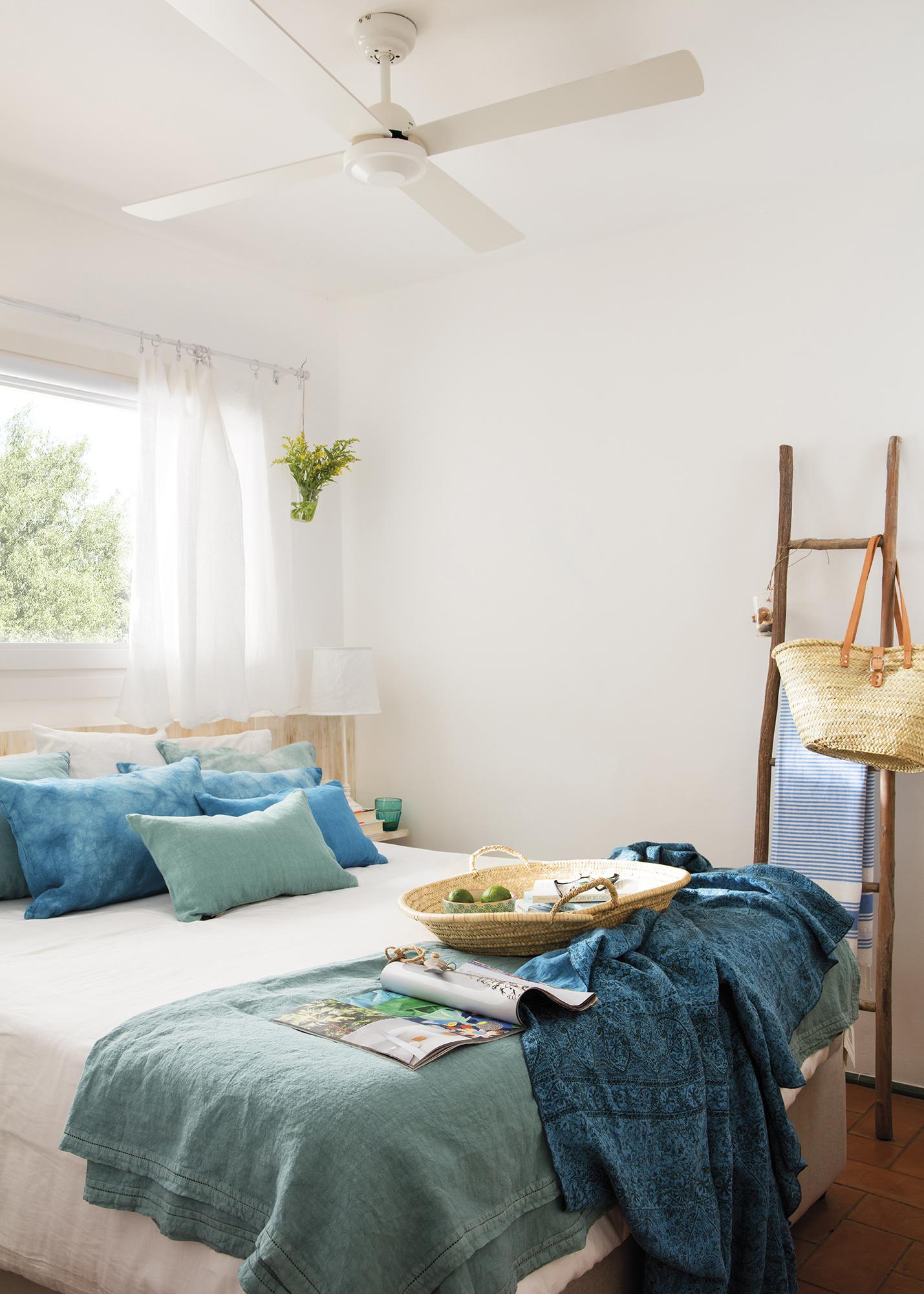Pano665-669. Sencillo y pequeño dormitorio con ropa de cama en blanco y cojines y plaids en tonos azules