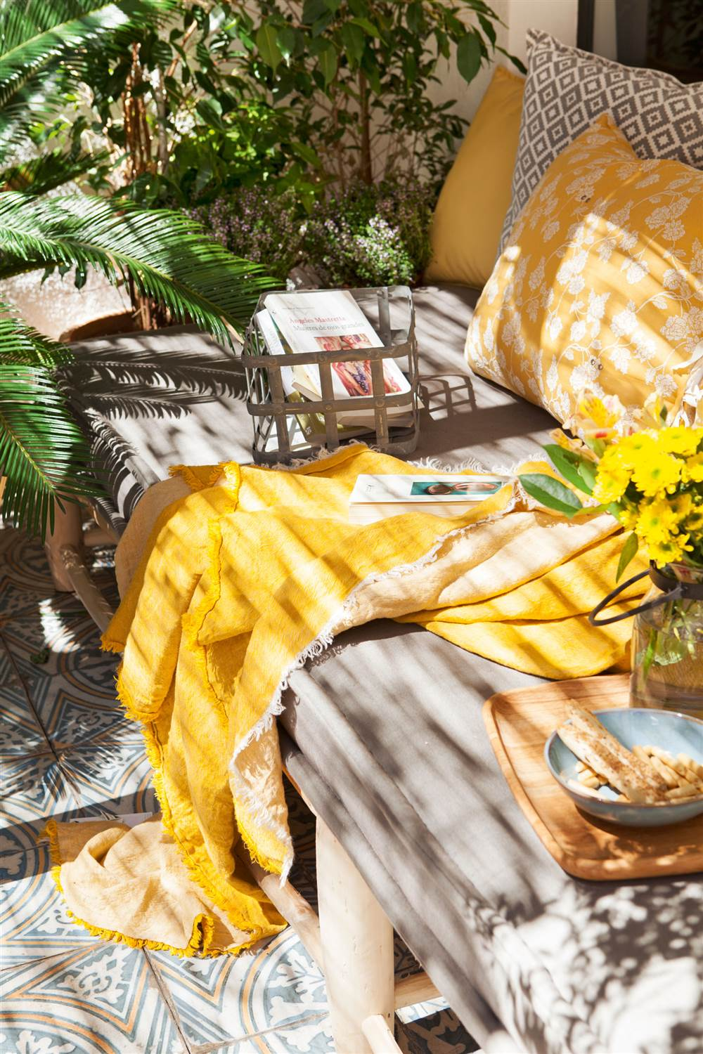 plaid y cojines en amarillo sobre un chill out exterior