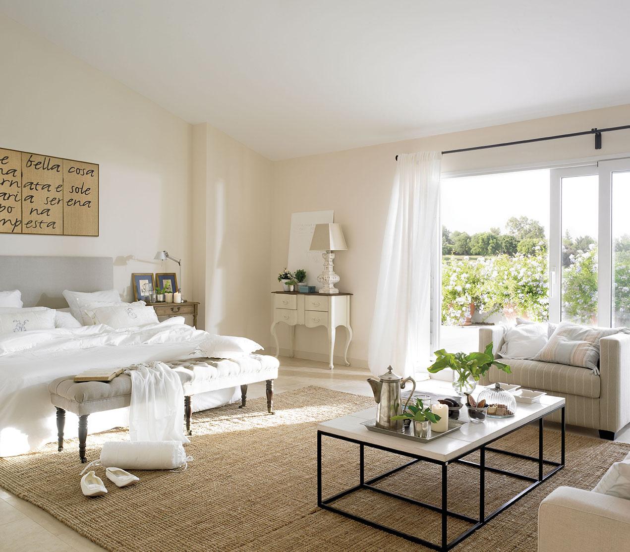 amplio dormitorio princiapal con una cama blanca y un zona de estar con sillones