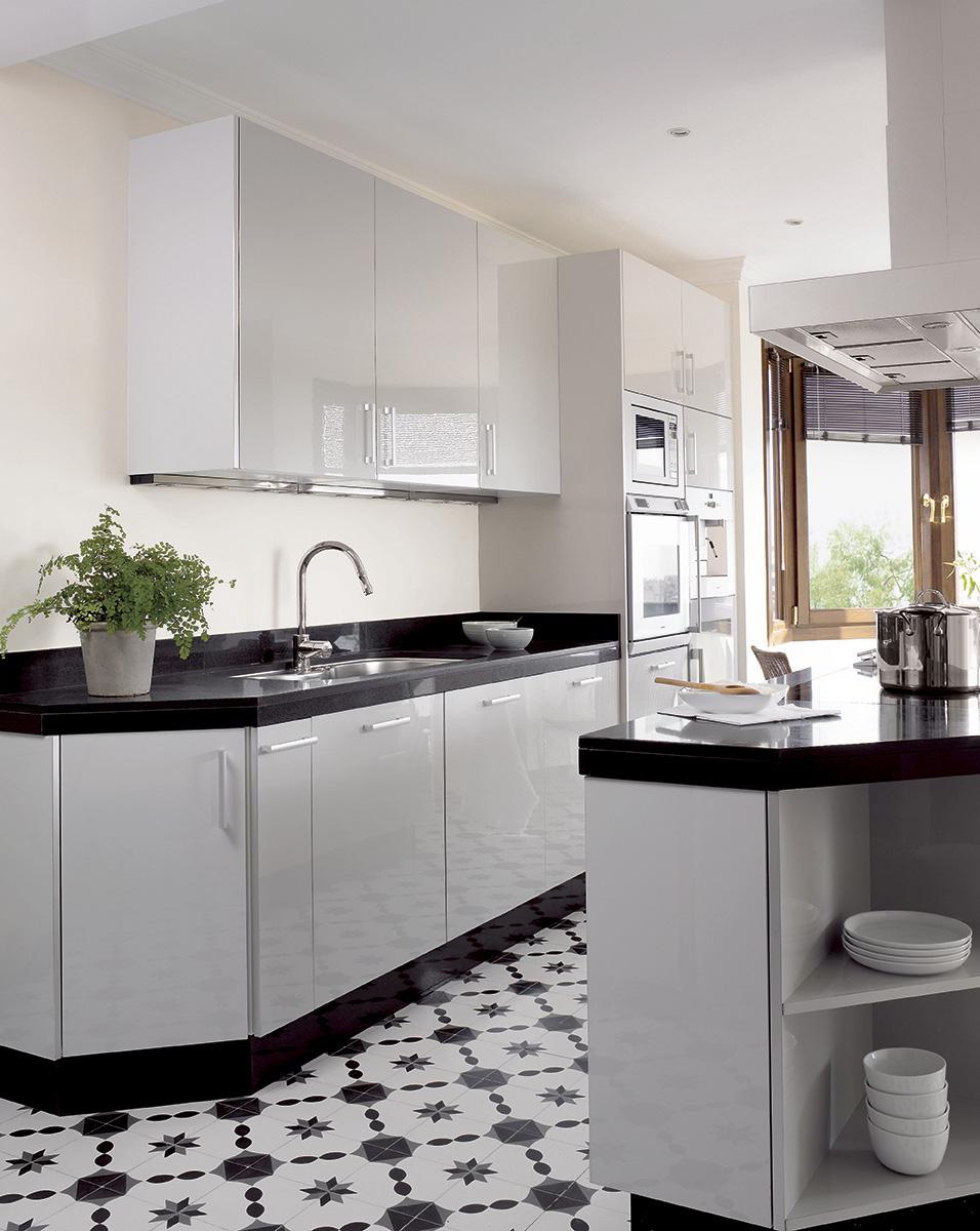 Cocina con mobiliario en blanco y encimera de granito negro sobre un suelo de