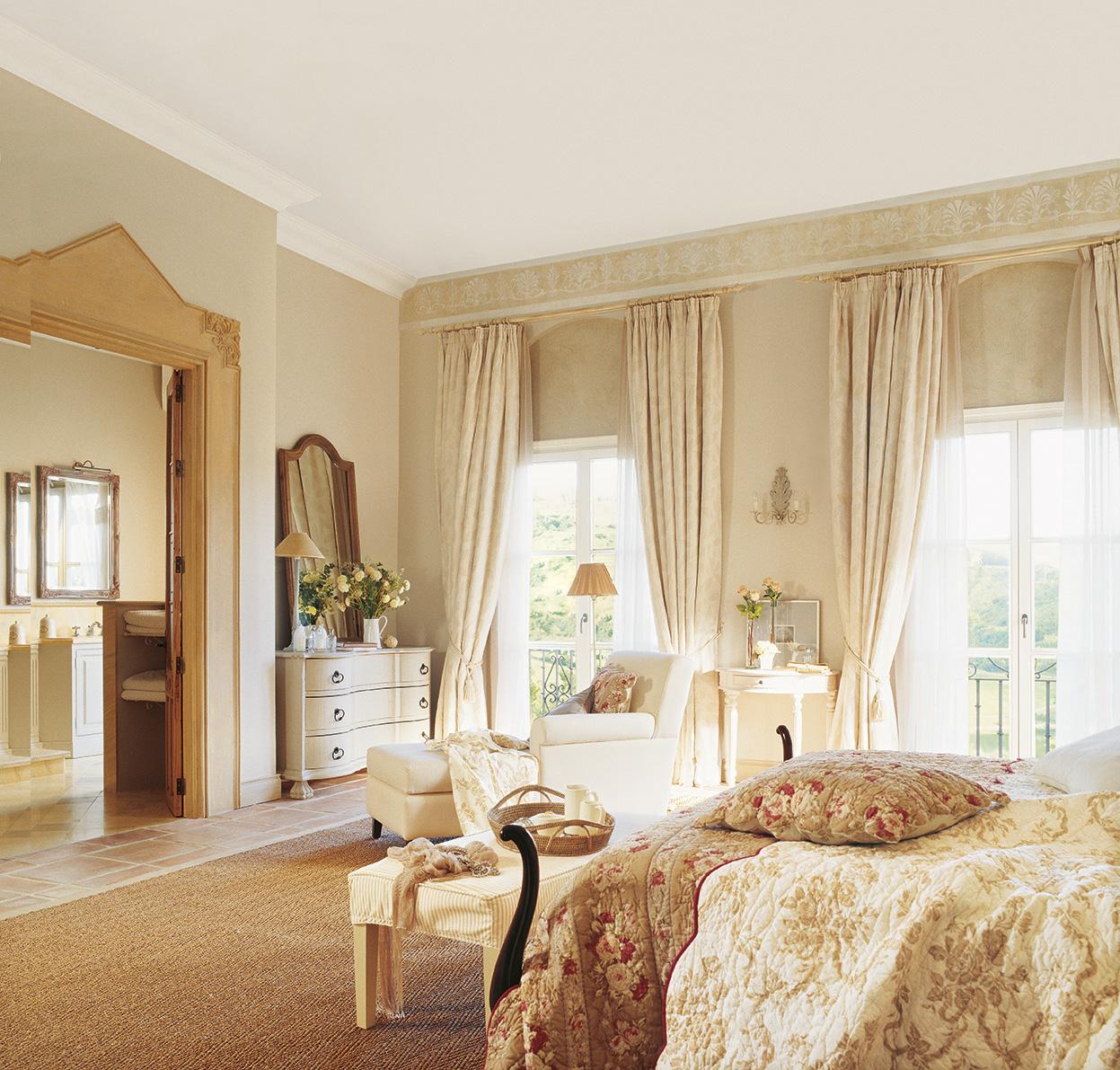 00161201. Dormitorio principal en tonos beige con balcones, chaise longue blanca y puerta con marco que comunica con el baño_00161201