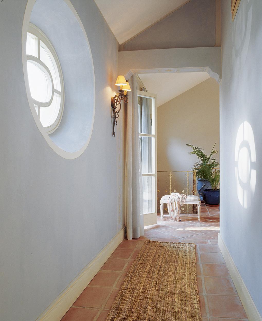 00161250. Pasillo con paredes en azul y una alfombra de mimbre sobre un suelo de baldosas_00161250