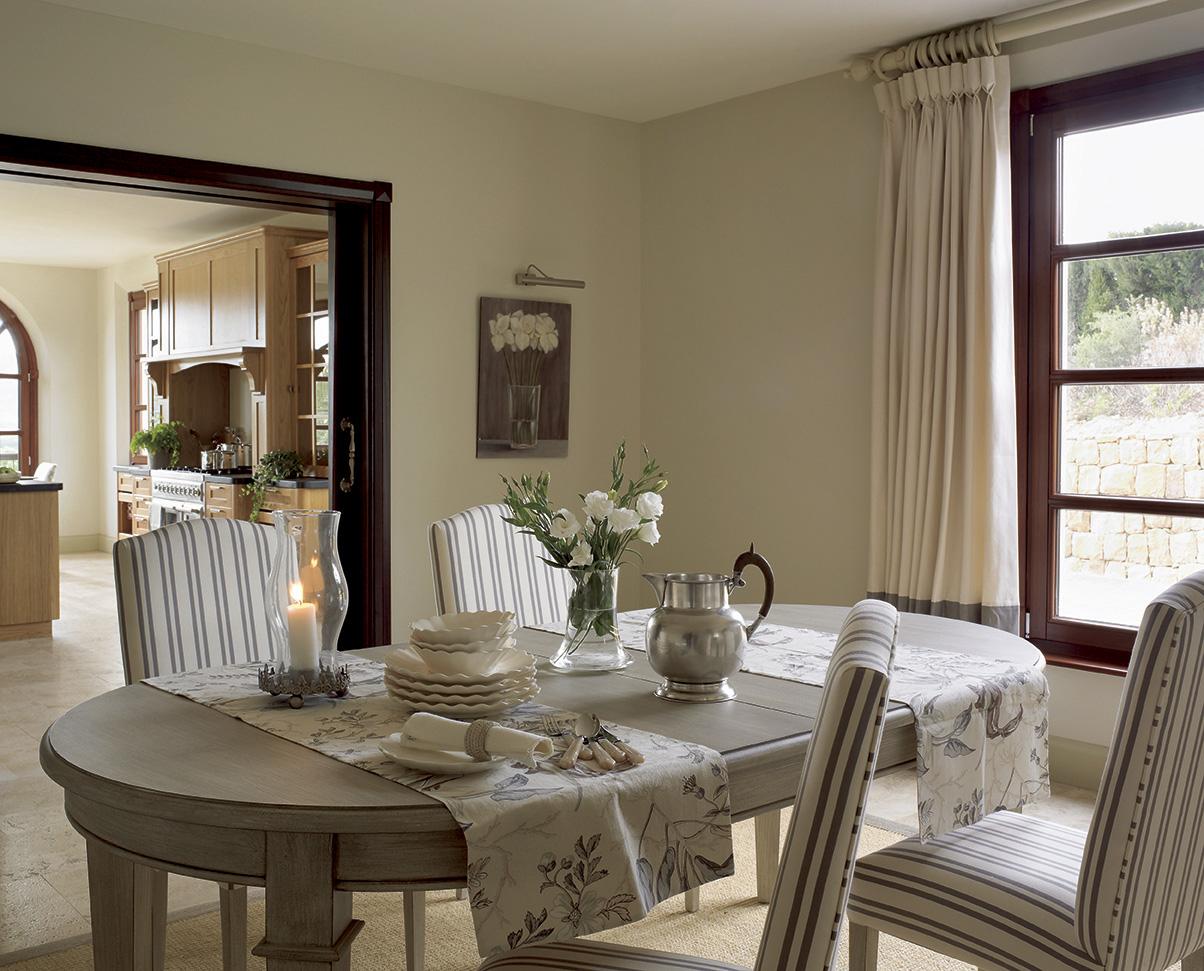 comedor en tonos grises con sillas tapizadas a rayas y con una puerta corredera