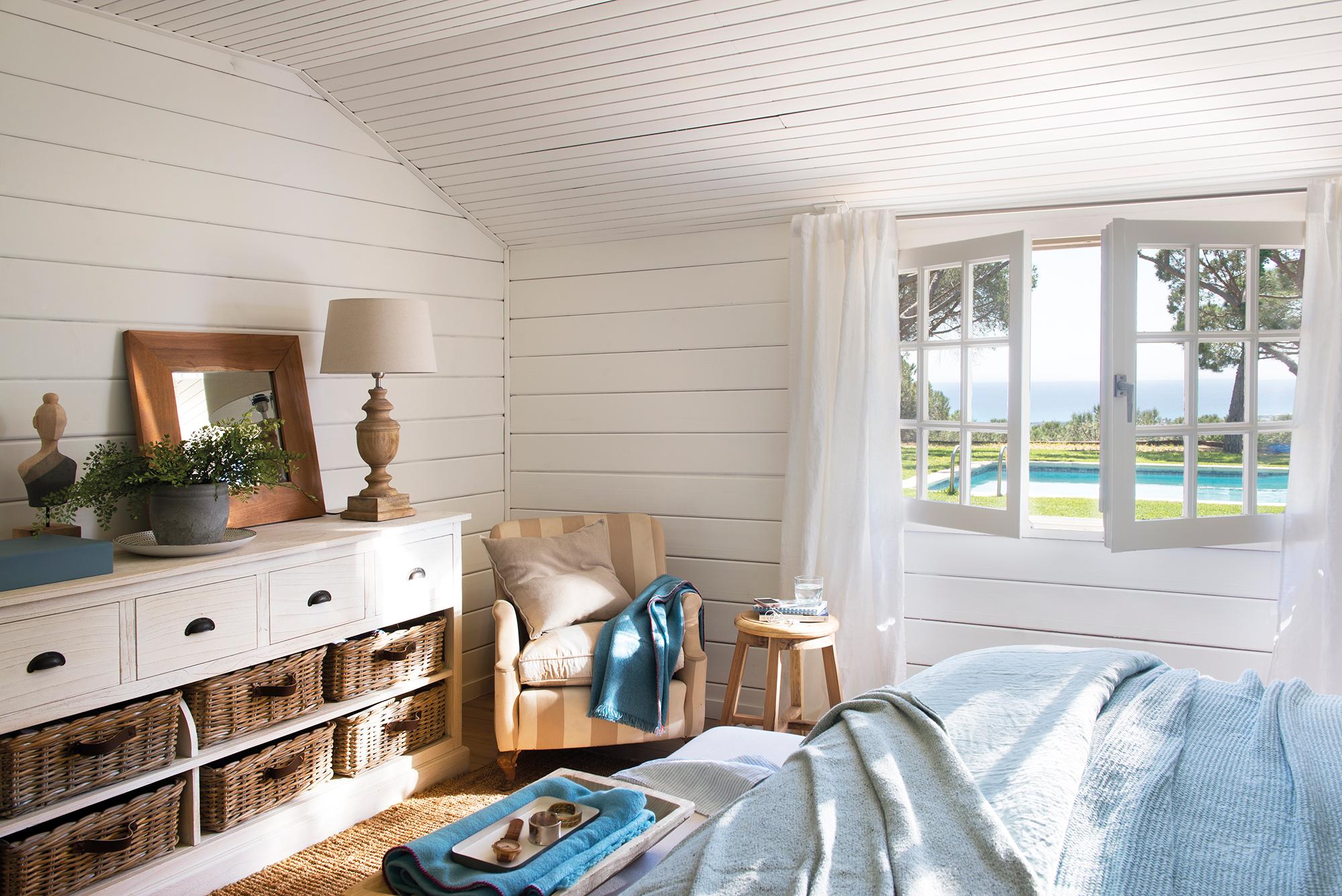 Dormitorio con paredes y suelo de listones de madera blanca y mueble bajo a pie de cama_458423