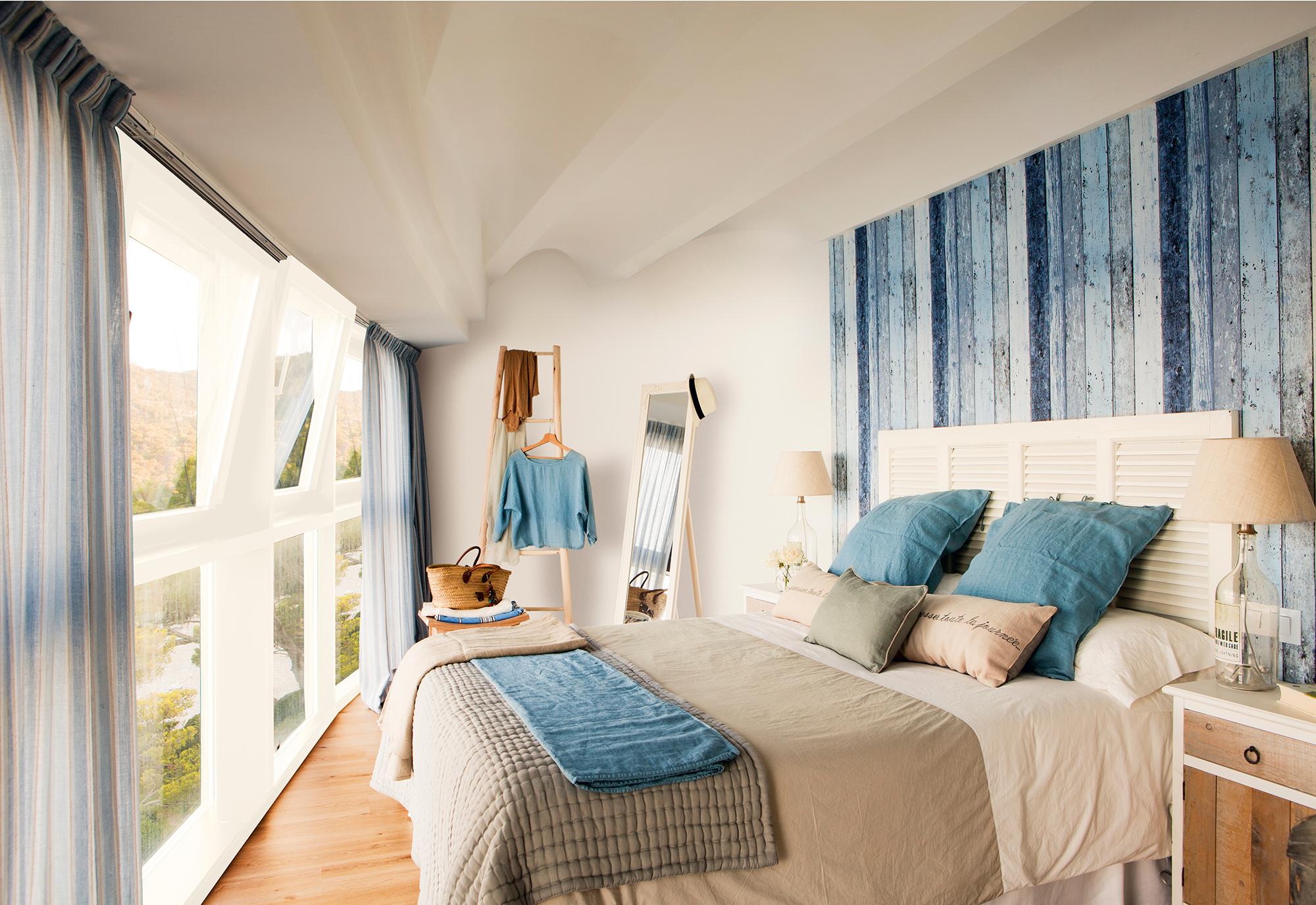 Dormitorio con ventanal a pie de cama y cabecero de listones de madera en azul_409306