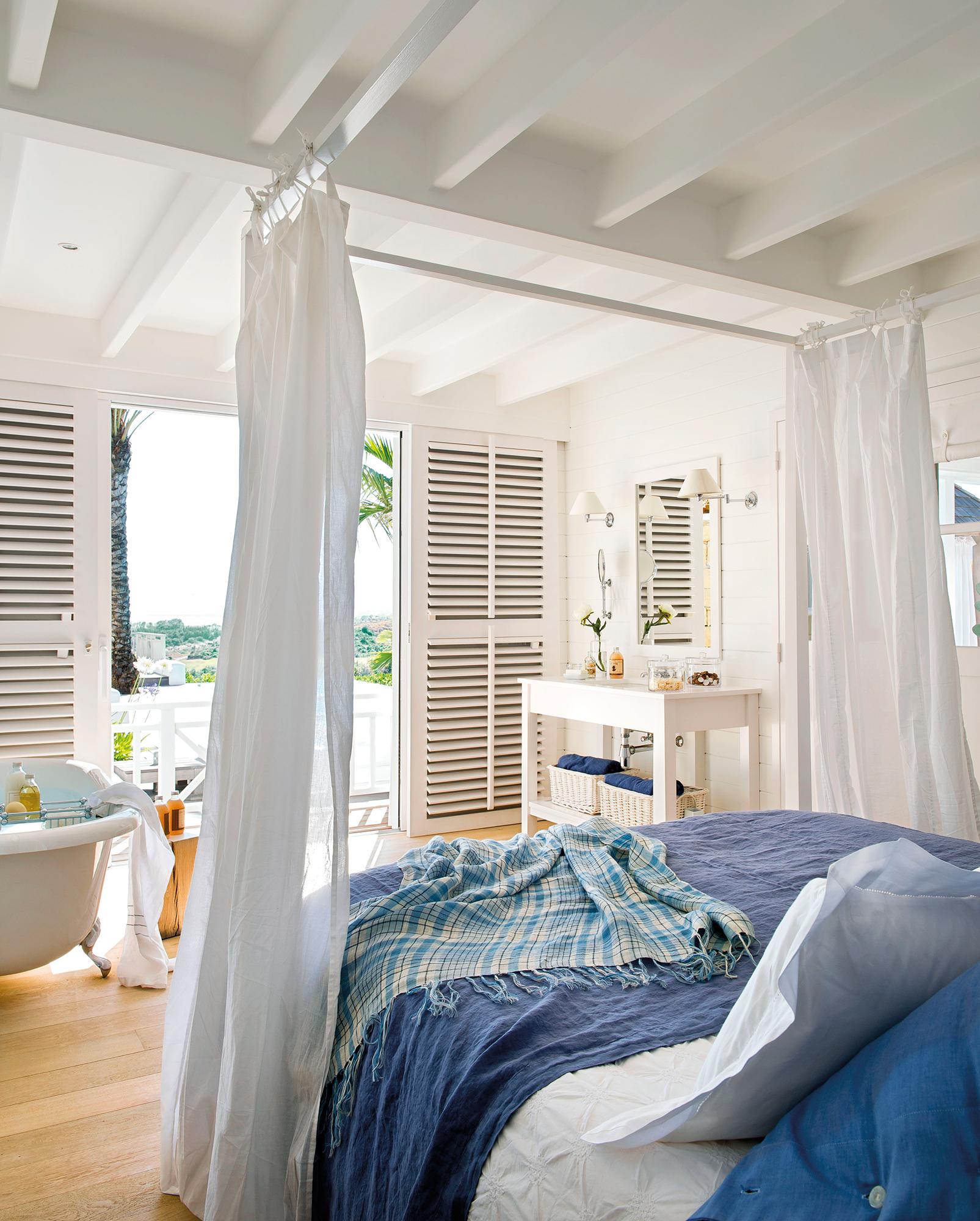 Dormitorio en blanco y detalles en azul con bañera con vistas al jardín_365839