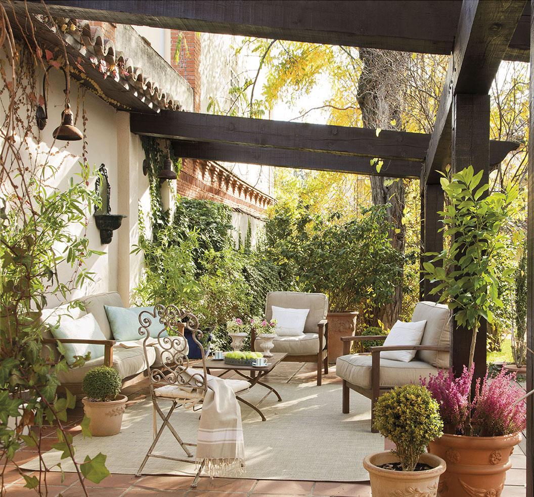 00312051. Terraza rodeada de vegetación con muebles de madera y cojines en beige_00312051