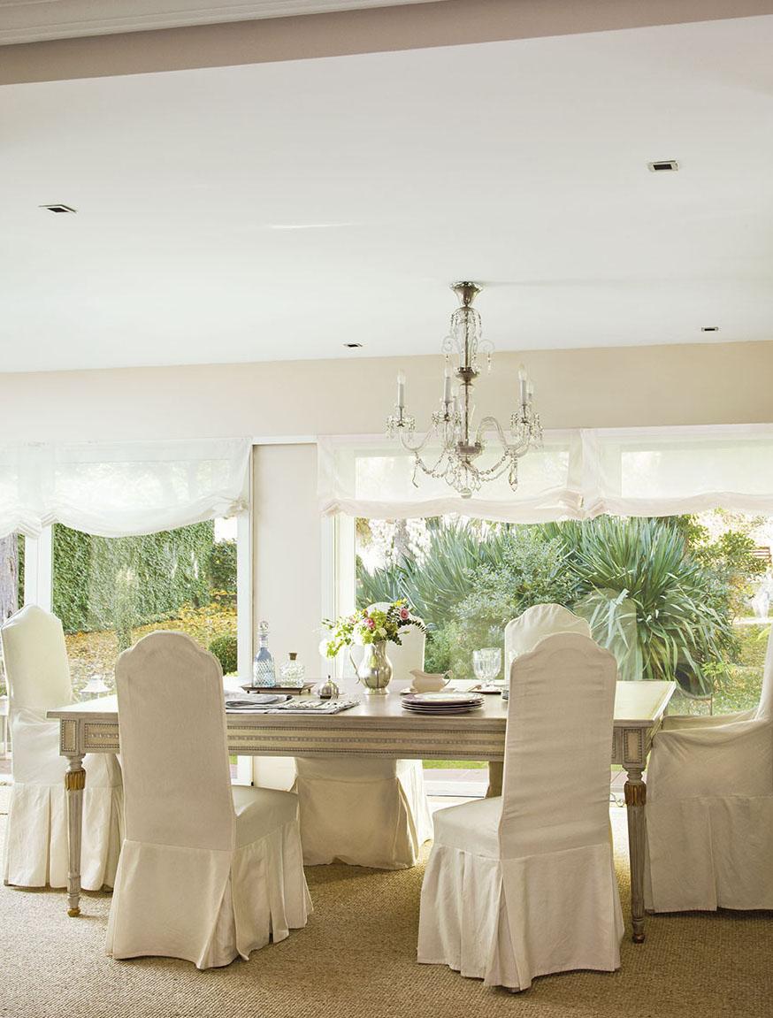 00312059. Comedor con sillas con fundas blancas, mesa de madera de estilo clásico y lámpara de techo de cristal_00312059