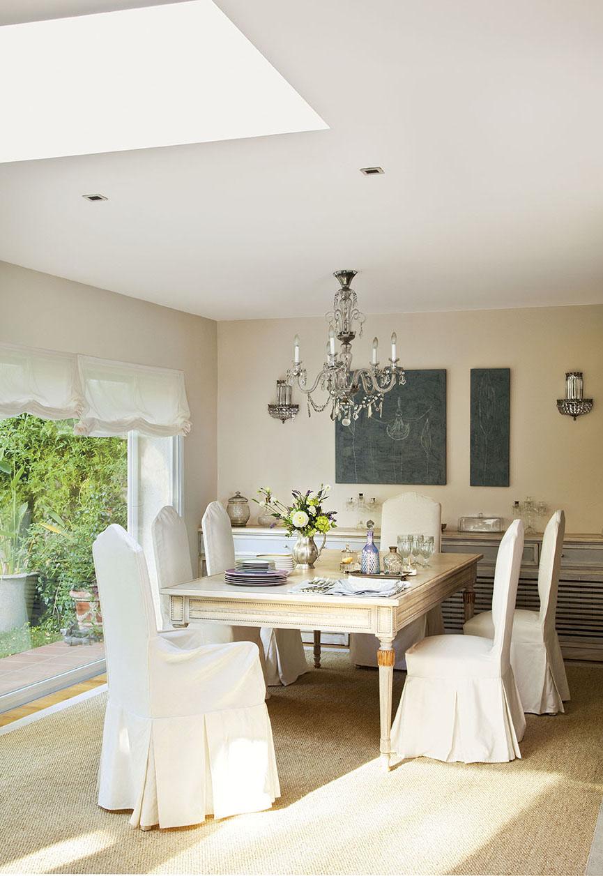 00312061. Comedor con sillas con fundas blancas, lámpara de techo de cristal y ventanal al jardín_00312061