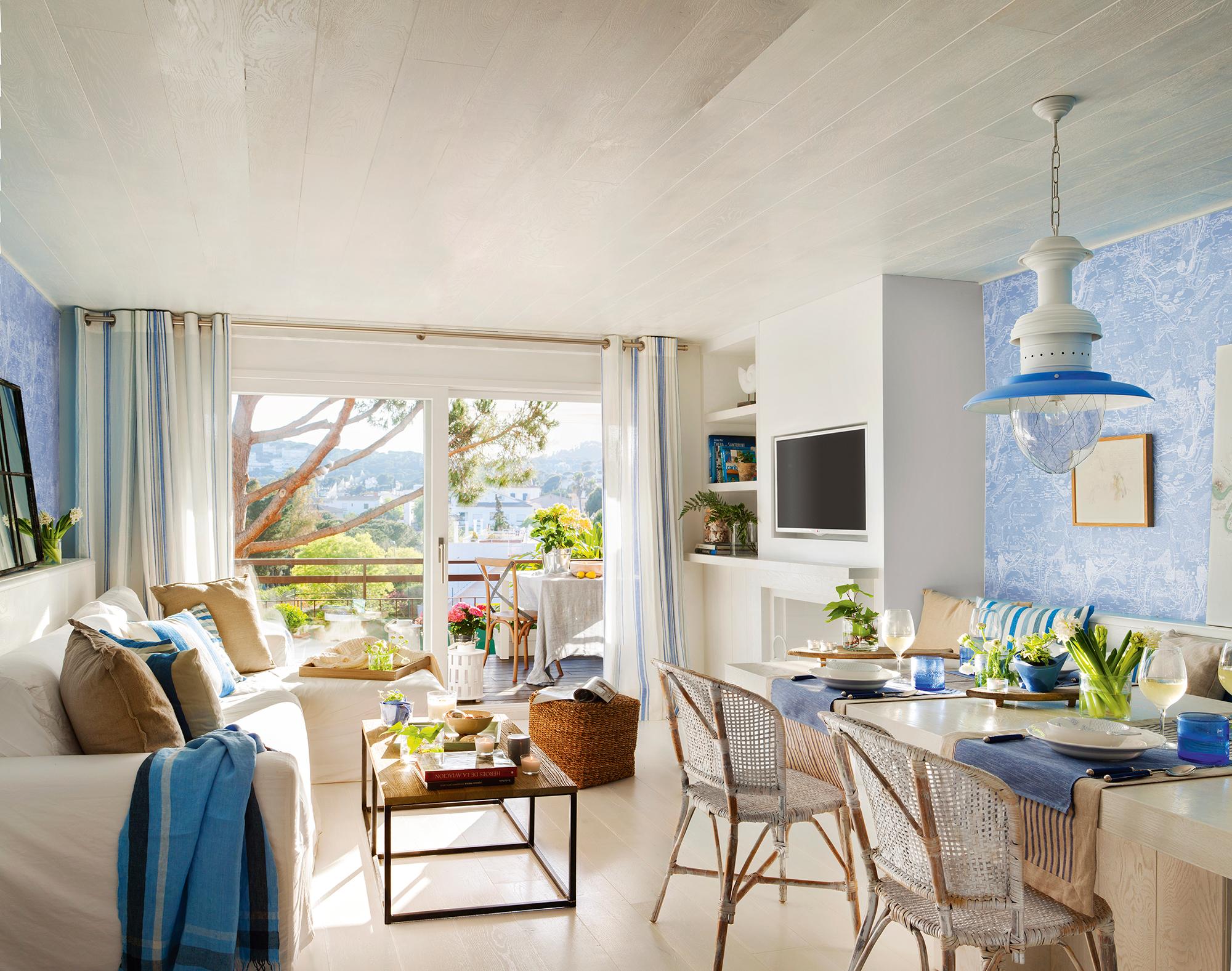 saln con comedor con paredes azules y muebles blancos