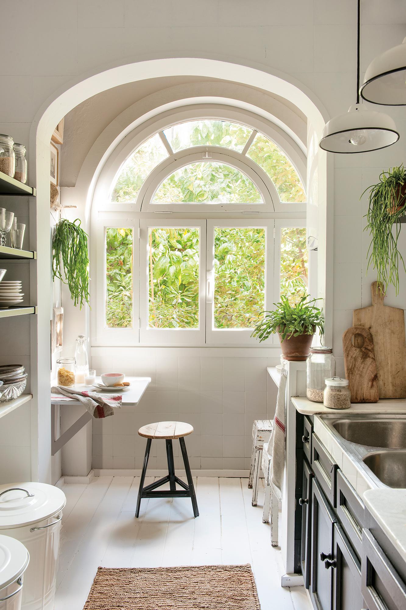 Cocina blanca con gran ventanal en forma de arco y muebles de cocina en negro_ 00451211