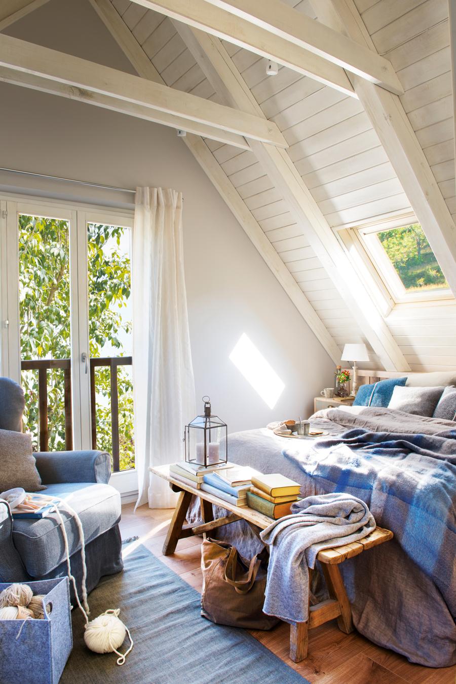 00442701. Dormitorio abuhardillado rústico con techos de madera en blanco, butaca gris y ropa de cama azul y gris 00442701
