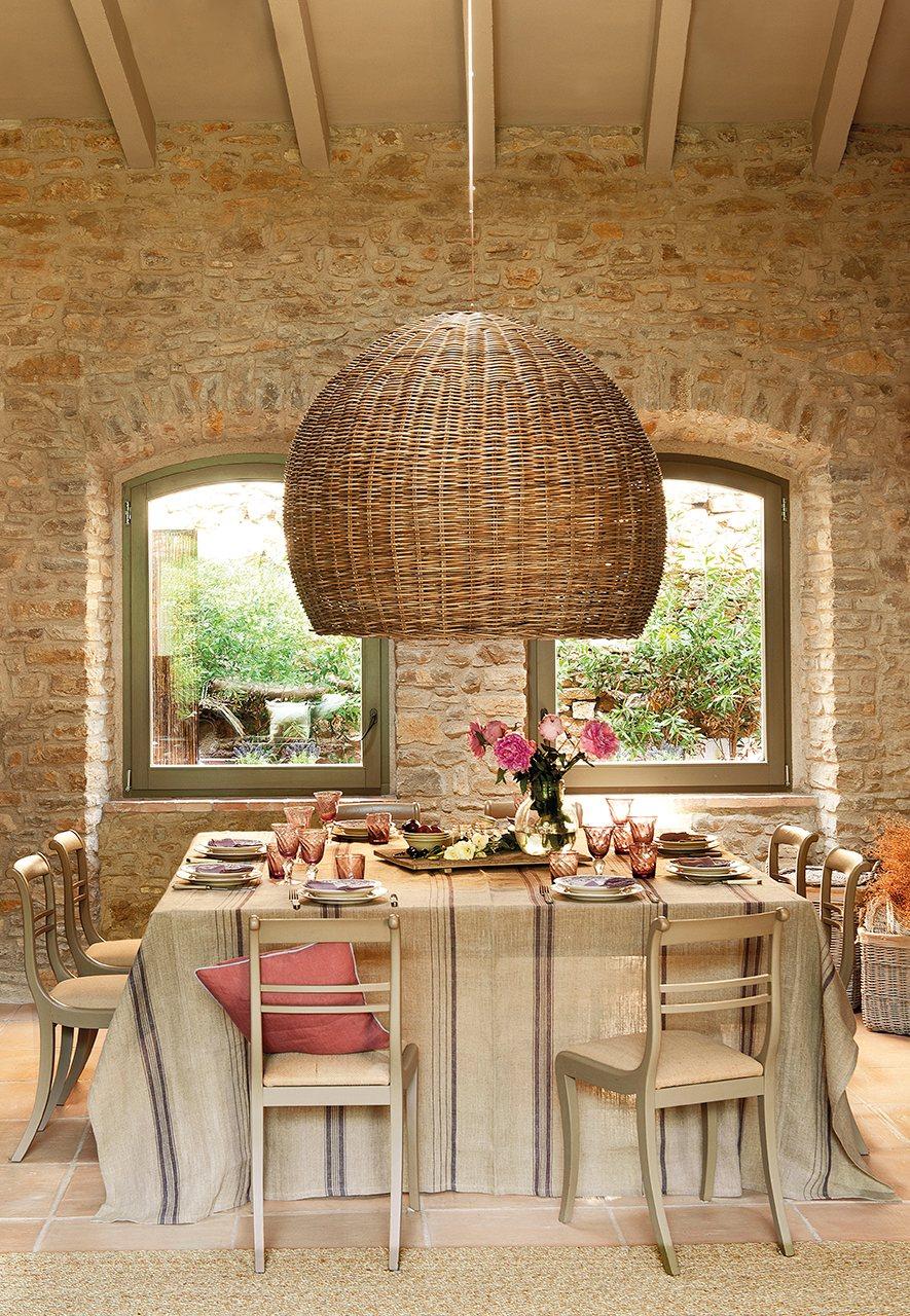 Comedor con paredes de piedra y gran lámpara de mimbre