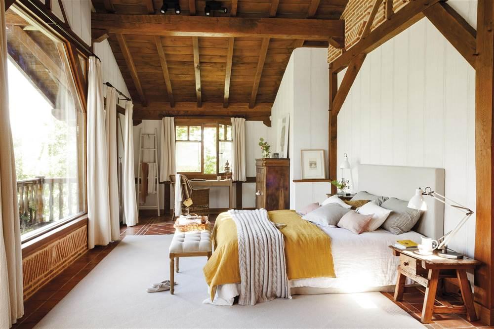 Dormitorio con gran ventanal, techo de madera y cama con banqueta a los pies