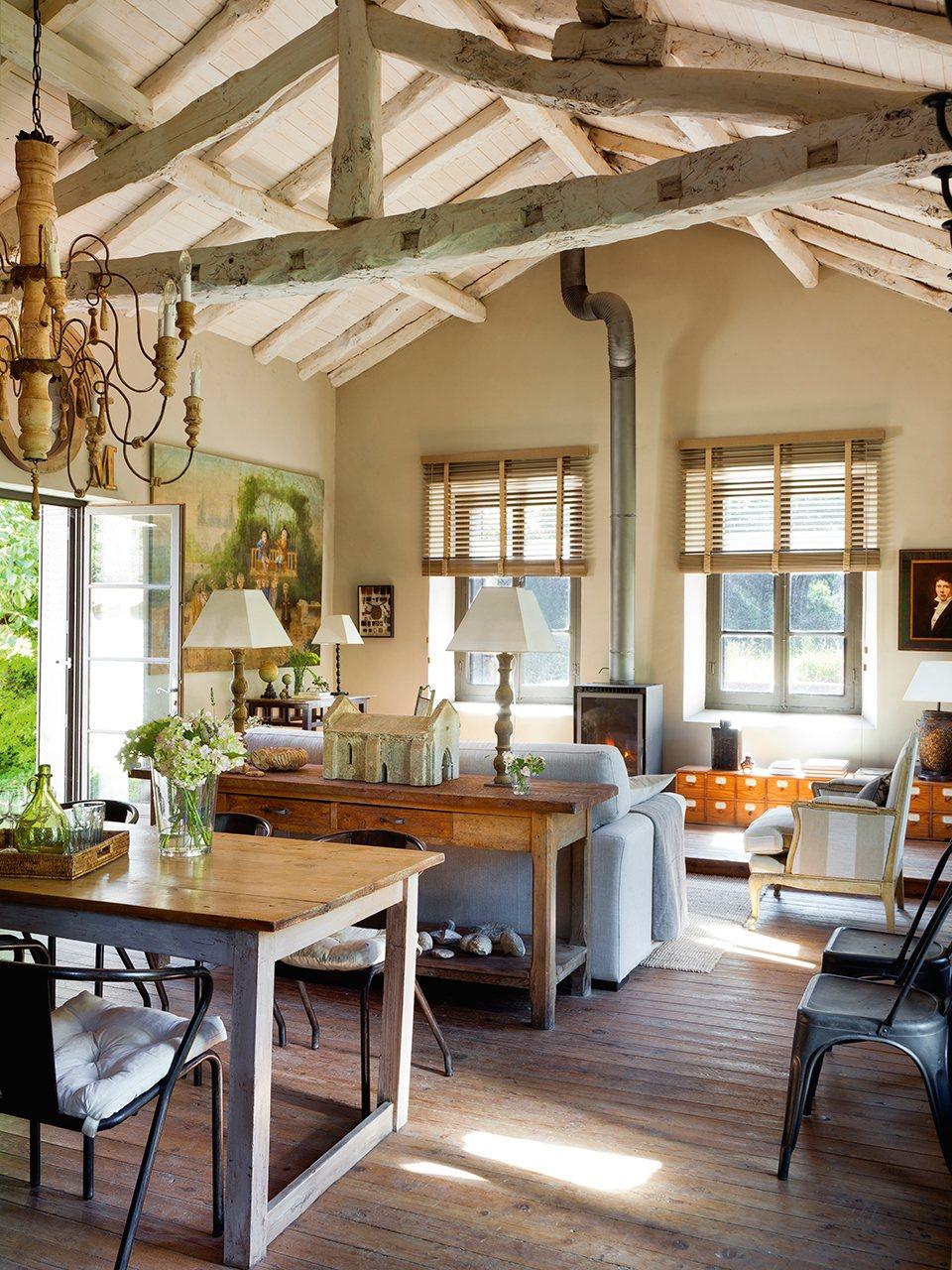 salon comedor con chimenea de hierro y techo con vigas vistas