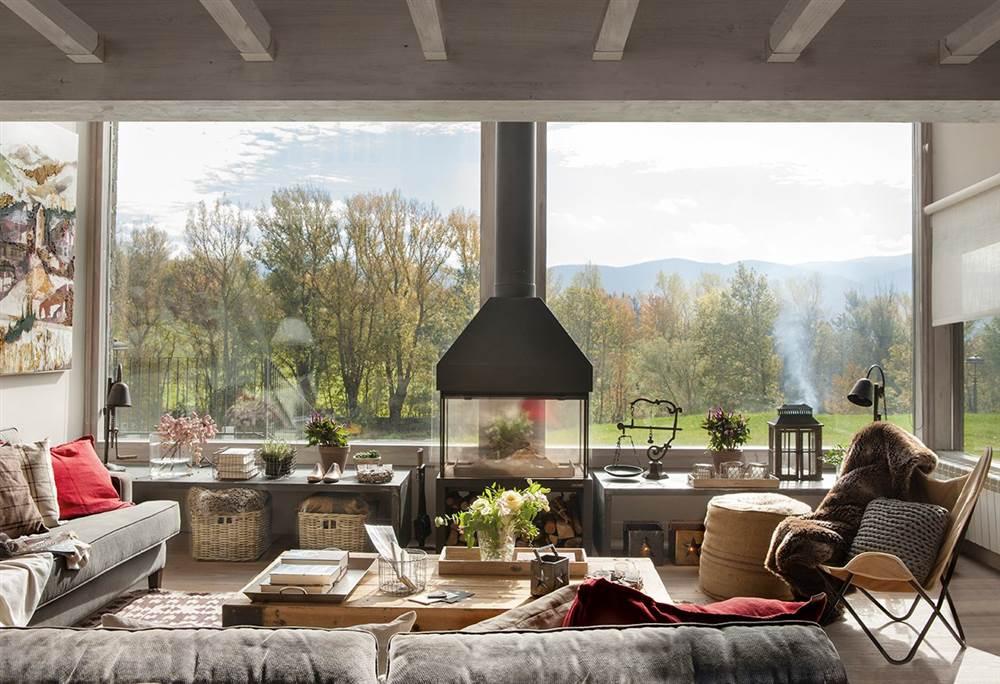 salon con chimenea de hierro y pared de cristal con vistas al bosque