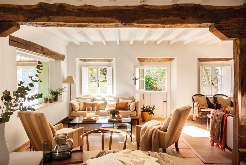 Salón con techos de madera con butacas y sofá