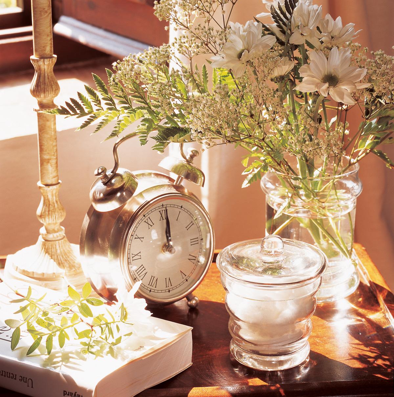 00150489. Reloj de mesa y flores sobre una mesa auxiliar_00150489