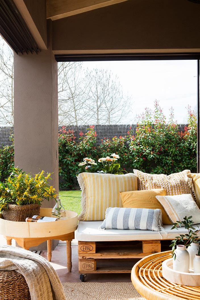 Una terraza llena de cojines igual a comodidad y estilo for Mesa de terraza con quitasol