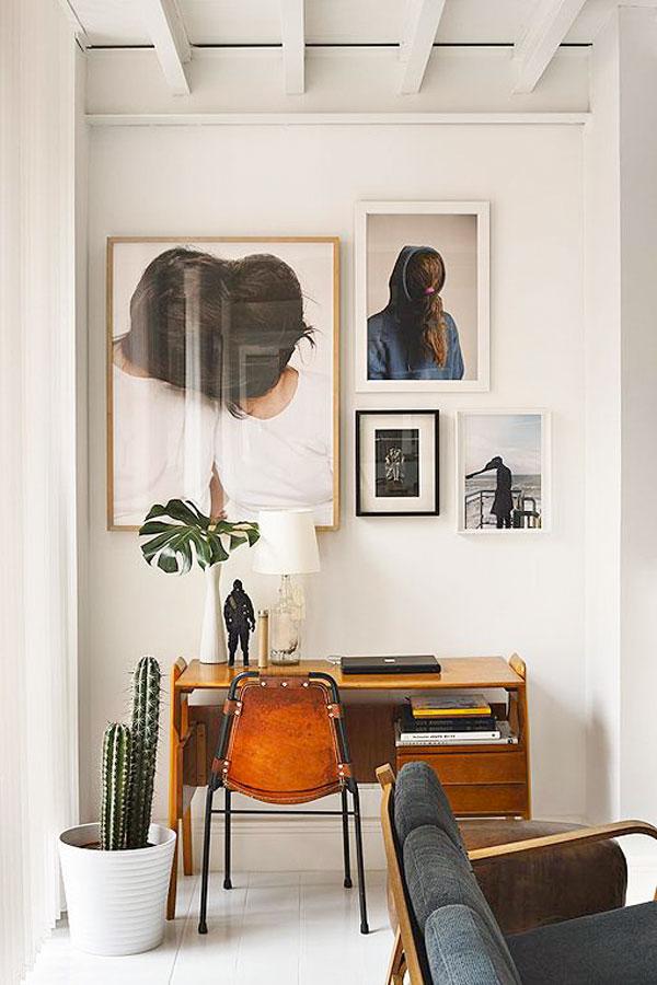 escritorio-de-madera-con-silla-de-cuero-y-jarrón-con-hoja-de-filodendro-o-monstera. Filodendro o monstera deliciosa