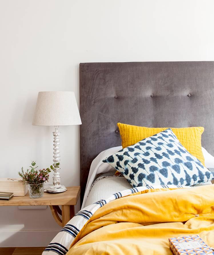 Cabecero gris capitoné y mesita de noche con lámpara de sobremesa y textiles mostaza y estampados_452042