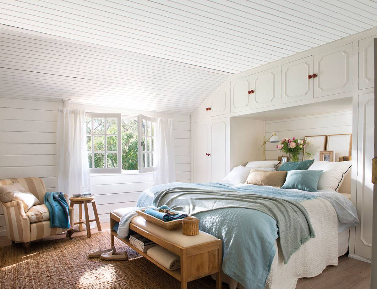 Dormitorio con banqueta madera en los pies de la cama y cabecero de obra con armario y tonos en Azul_458454
