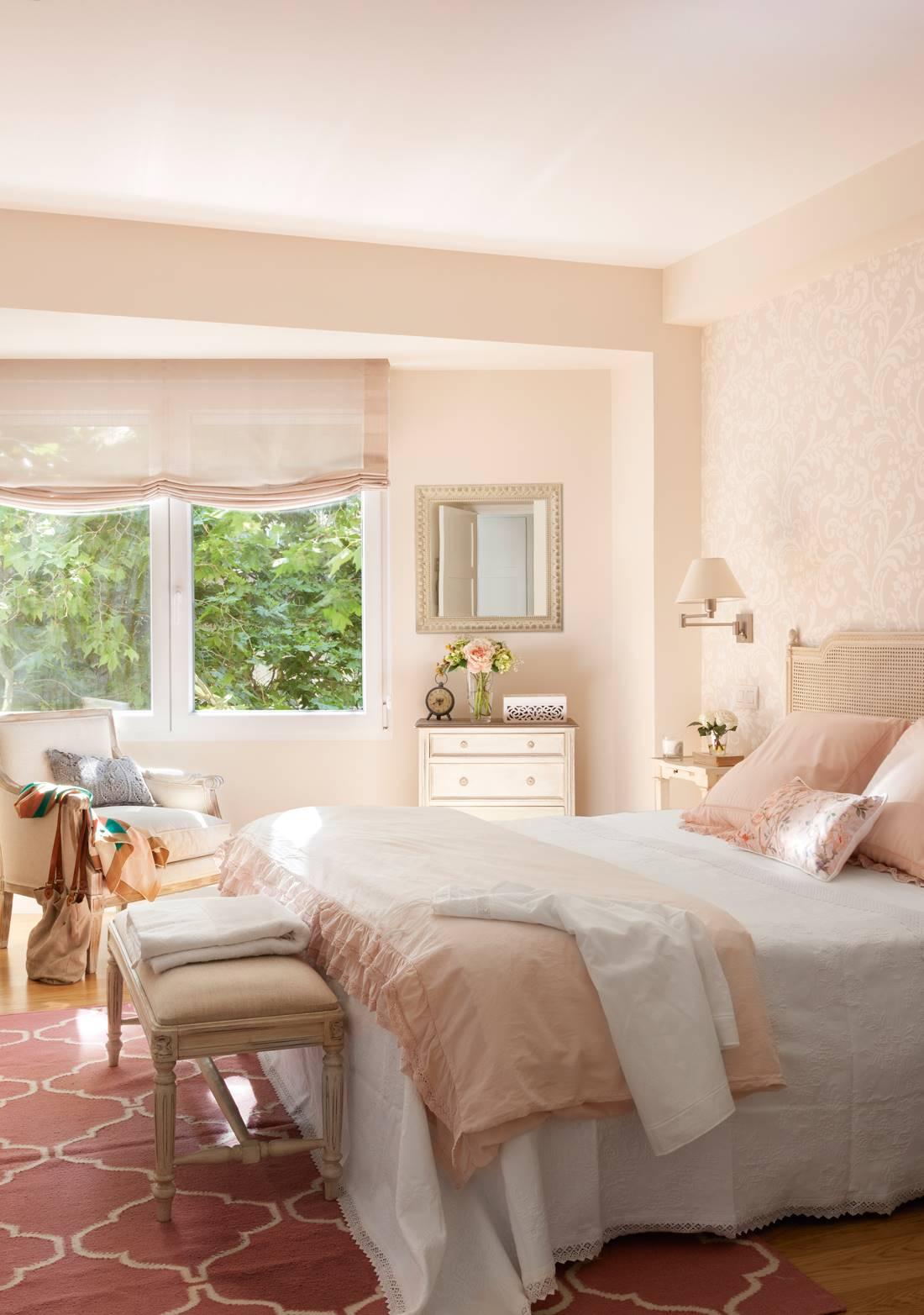 Dormitorio con banqueta pies de la cama y estores con tonos rosa_410500
